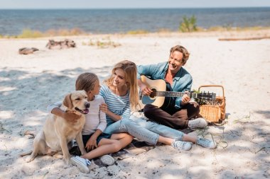 Woman hugging daughter with golden retriever while husband playing acoustic guitar on beach