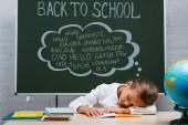 kimerült iskolás lány alszik íróasztal közelében földgömb és tábla vissza az iskolába, és üdvözlő levél