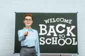 Lehrerin blickt in Kamera und zeigt mit Finger auf Kreidetafel mit Willkommensgruß zurück zur Schule