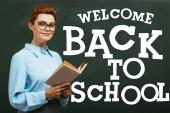 Fotografie Lehrerin mit Brille hält Buch neben Tafel mit Willkommensgruß zurück zur Schule im Klassenzimmer