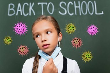 Selective focus of exhausted schoolgirl taking off protective mask near chalkboard with back to school lettering and virus illustration stock vector