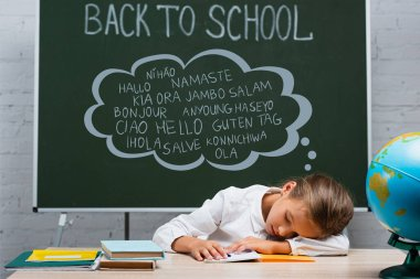 Exhausted schoolgirl sleeping at desk near globe and chalkboard with back to school and greeting lettering stock vector