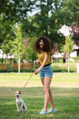 Selective focus of young woman looking away and keeping dog on leash