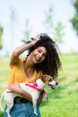 fröhliche, brünette Frau berührt lockiges Haar, während sie Jack Russell Terrier-Hund hält