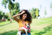 joyful woman touching curly hair while holding jack russell terrier dog in park