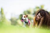 selektivní zaměření kudrnaté ženy smích při odpočinku s jack Russell teriér pes na trávníku