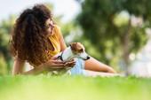 selektiver Fokus der lockigen Frau, die wegschaut und lacht, während sie mit Jack Russell Terrier-Hund auf dem Rasen liegt