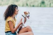 Seitenansicht einer aufgeregten Frau im Sommeroutfit, die in der Nähe des Sees mit Jack Russell Terrier-Hund sitzt