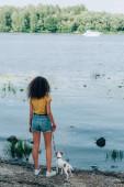 Rückansicht einer jungen Frau im Sommer-Outfit mit Jack Russell Terrier Hund an der Leine in der Nähe des Flusses