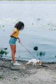 curly woman in summer outfit walking with jack russell terrier dog on leash near lake