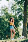 fröhliche junge Frau im Sommeroutfit spaziert mit Jack Russell Terrier Hund im Park und telefoniert
