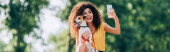 Photo horizontal concept of excited woman taking selfie on mobile phone with jack russell terrier dog