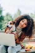 joyful freelancer mazlení jack Russell teriér pes zatímco sedí na lavičce s notebookem