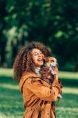 Junge Frau im Regenmantel umarmt Jack Russell Terrier im Park