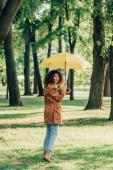 Selektivní zaměření ženy s deštníkem při pohledu do kamery na louce v parku