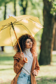 Curly woman in raincoat looking away while holding umbrella in park