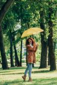 Mladá žena v podzimním oblečení drží žlutý deštník, zatímco stojí na trávě v parku