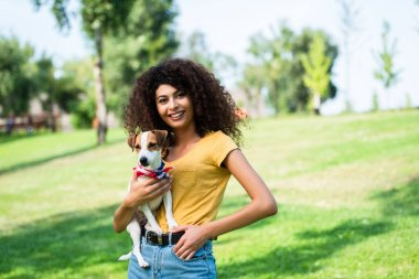 young woman in summer outfit standing with hand in pocket while holding jack russell terrier dog in park