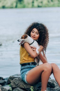 brunette, curly woman in summer outfit holding jack russell terrier dog while sitting on stones near river