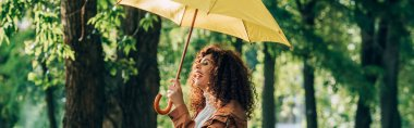 Panoramic shot of curly woman laughing while holding yellow umbrella in park stock vector