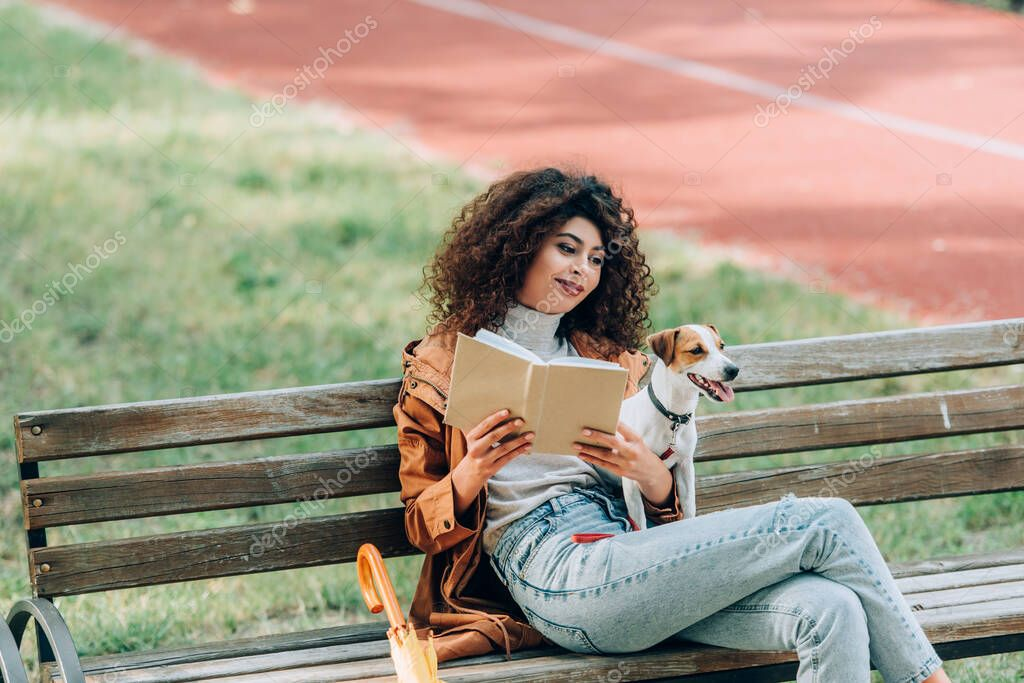 Stylish woman reading book while sitting on bench in park with jack russell terrier dog stock vector