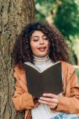 Szelektív fókusz barna nő esőkabátban nézi notebook mellett fa a parkban