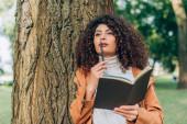 Selektivní zaměření zasněné ženy v pláštěnce držící pero a zápisník u stromu