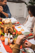 selective focus of man talking to african american daughter during thanksgiving dinner with family