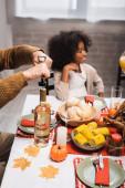 selective focus of senior man opening bottle of white wine near african american granddaughter while celebrating thanksgiving