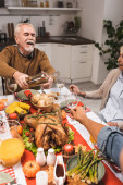 selective focus of excited senior man pouring white wine during thanksgiving dinner with family
