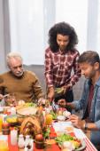 Afričanky americká žena servírující jídlo na talíři muže na díkůvzdání
