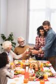 joyful multicultural family clinking wine glasses during thanksgiving dinner