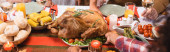 Photo Horizontal image of african american woman putting turkey on table near family during thanksgiving dinner
