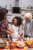 Selective focus of african american woman holding cherry tomatoes near daughter and elderly woman during thanksgiving