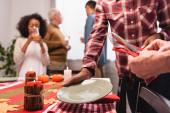 Selektiver Fokus multiethnischer Frauen beim Servieren des Tisches während der Erntedankfeier