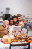 Selective focus of multiethnic family having video call on digital tablet during thanksgiving celebration