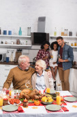 Selective focus of elderly man looking at wife while celebrating thanksgiving with multiethnic family