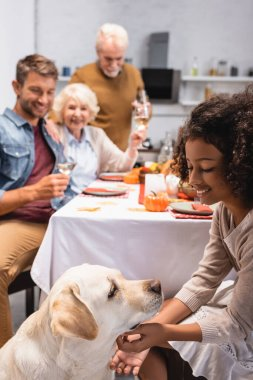 Selective focus of joyful african american girl stroking golden retriever during celebration of thanksgiving day with family stock vector