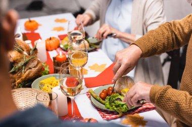 Selective focus of senior man cutting lettuce near family during thanksgiving dinner stock vector