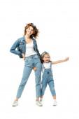 dcera v džínové oblečení objímání matka noha s nataženou rukou izolované na bílém