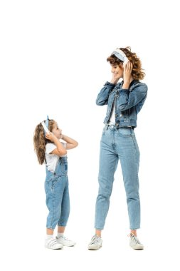 mother and daughter in denim outfits listening music in headphones and looking at each other isolated on white