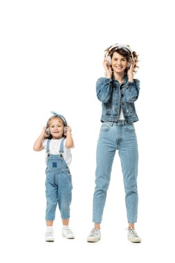 Mother and daughter in denim outfits listening music in headphones isolated on white stock vector