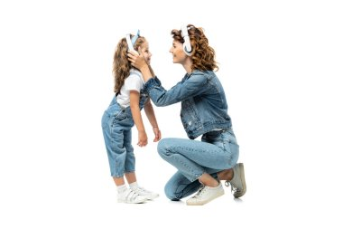 side view of mother and daughter in denim outfits listening music in headphones face to face isolated on white
