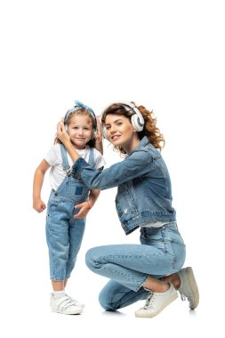 mother and daughter in denim outfits listening music in headphones isolated on white