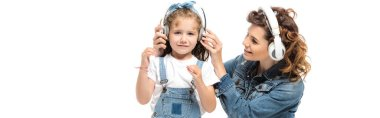 mother and daughter in denim outfits listening music in headphones isolated on white, panoramic shot
