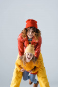 mother and daughter in colorful red and yellow outfits smiling isolated on grey
