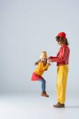 boční pohled na matku a dceru v barevné červené a žluté oblečení hraje na šedém pozadí