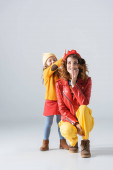 mother and daughter in colorful red and yellow outfits having fun on grey background