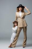 elegantní matka a dcera v bílých a béžových oblečení pózují na šedé