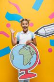 radostné školačka mává rukou při držení glóbus maquette na žlutém pozadí s papírem řezané tužkou a barevné prvky